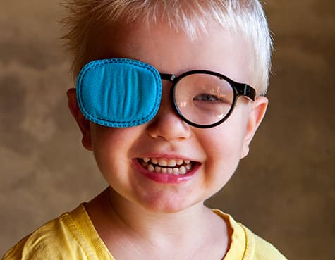 Boy wearing glasses with one lens blocked to treat lazy eye