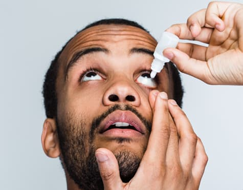 African American man using eye drops for glaucoma treatment