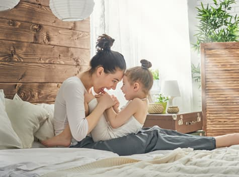 Woman playing with her child on bed
